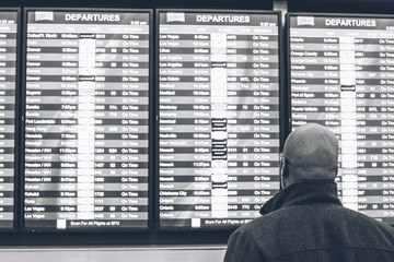 Man checking his flight timetable on the departure board at the airport