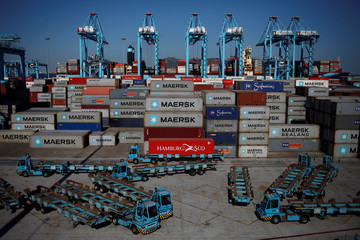 A worker drives a truck with a container past idle trucks, cranes and containers at APM Terminals in the port of Algeciras