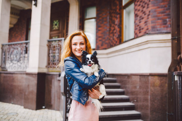 A beautiful young woman with red long hair is holding a small, cute funny big-eyed dog of two flowers, a black-and-white pet of the breed of hichuahua against a house of red brick in summer