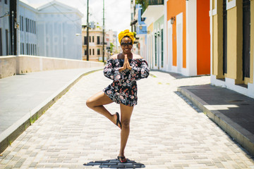 Smiling young woman in yoga pose on colorful street
