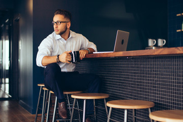 Businessman holding coffee mug in office cafeteria