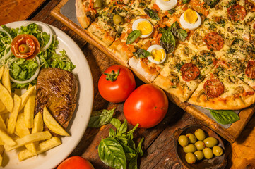 Above view of group of fastfood, grilled beef, pizza and fry potatos, with tomatoes over a wooden table