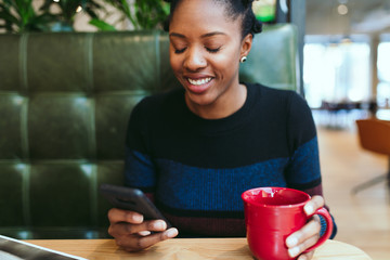 Young businesswoman using smartphone while having coffee in the office