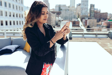 Businesswoman using smartphone while standing on office rooftop