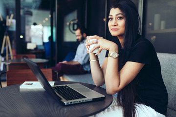 Young businesswoman having coffee while sitting in office