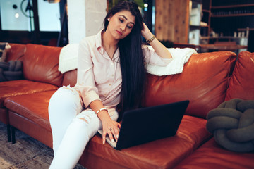 Young businesswoman working on laptop while sitting on sofa