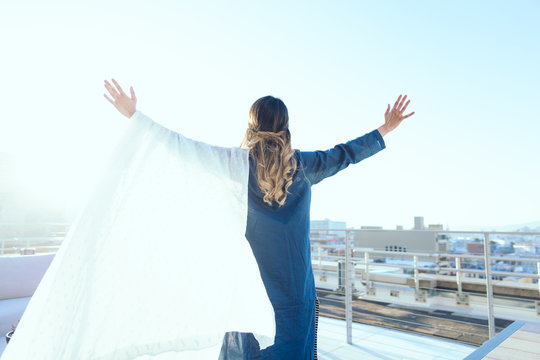 Rear view of woman standing on rooftop