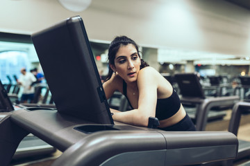Young woman leaning on treadmill in the gym