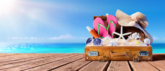 Beach Accessories In Suitcase On Wooden Pier - Travel Concept