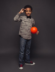 Portrait of boy holding ball against purple background