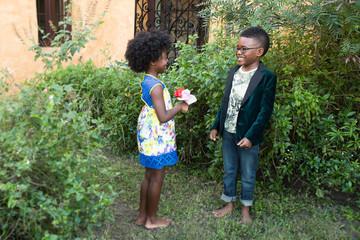 Fototapete - Boy and girl standing in the backyard garden