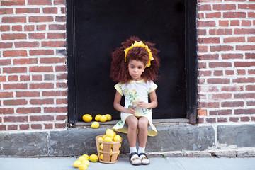 Portrait of girl sitting on doorstep with basket of lemons