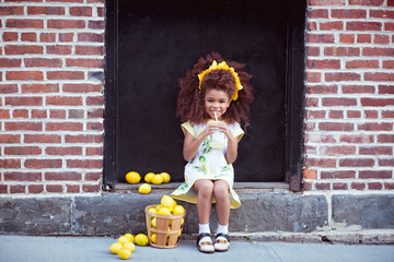 Portrait of happy girl sitting on doorstep with basket of lemons