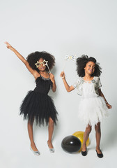 Playful girls standing against white background