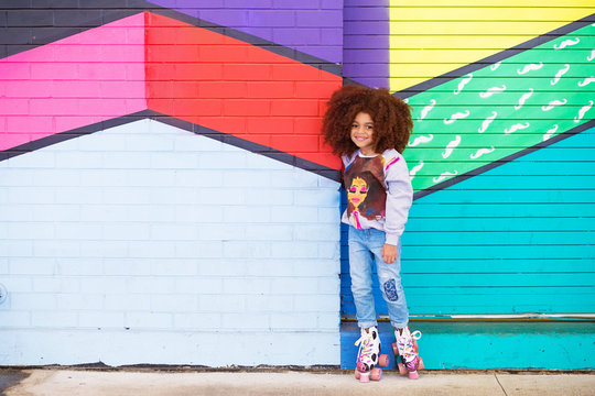 Portrait of cute girl standing against colorful background