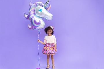 Girl holding unicorn balloon against purple background