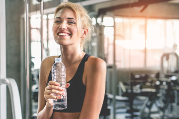 Happy wellbeing woman drink water after workout in gym. Wall mural