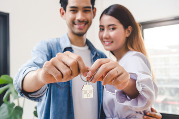 Relocation and beginning new life. Asian couple showing keys apartment after purchase and moving in new room together.