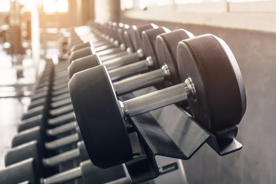 Rack of many sizes of dumbbell in gym sport club.