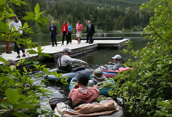 G7 Development Ministers walk down a dock near a group of people fly fishing on Nita Lake during the family photo at the G7 Finance Ministers summit in Whistler