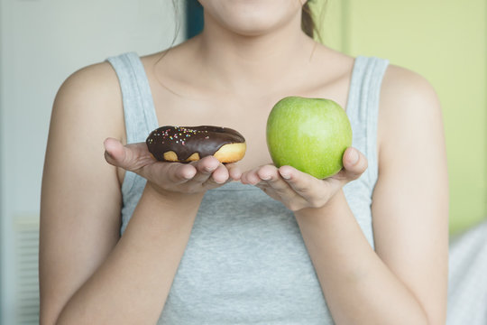 Choose a right choice for good health. Women is choosing choice between donut and green apple during her dieting session.
