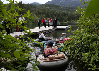 G7 Development Ministers walk down a dock near a group of people fly fishing on Nita Lake during the family photo at the G7 Finance Ministers summit in Whistler,