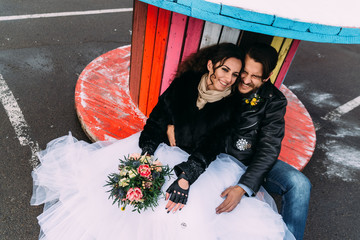 Wedding in the style of rock. Rocker or Biker wedding. Guys with stylish leather jackets. It's a rock'n'roll baby A sweet couple is photographed against the background of graffiti.