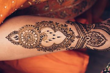 traditional Mehndi henna pattern on female leg. Close-up photo..