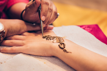 Process of applying traditional Mehndi henna on female hand. Close-up photo..