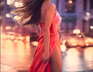 Beautiful woman wearing sexy silk evening dress posing on night city street of New York