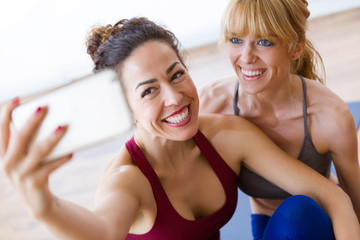 Two pretty young sporty women taking a selfie after yoga session at home.