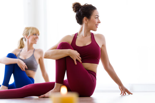 Two pretty young women practicing yoga at home. Marichyasana pose.