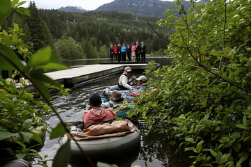 G7 Development Ministers pose for a picture near a group of people fly fishing on Nita Lake during the family photo at the G7 Finance Ministers summit in Whistler