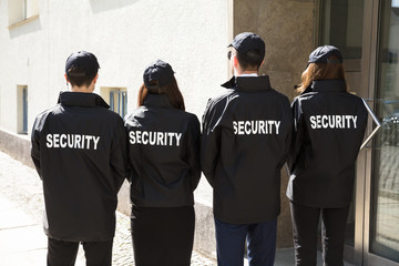 Rear View Of Security Guards Wearing Uniform