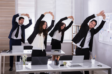 Businesspeople Doing Exercise Behind Desk