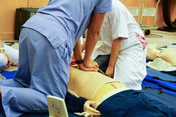 A blue dress trainee nurse performing chest compression on a mannequin during CPR training course