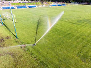 water jets sprinkling green football field in sunny day