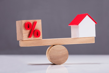 Seesaw Showing Balance Between Percentage Symbol And House Model