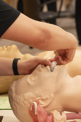 A trainer demonstrate how to place oral airway on a CPR model.