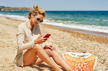 Young woman on the sea coast with mobile phone
