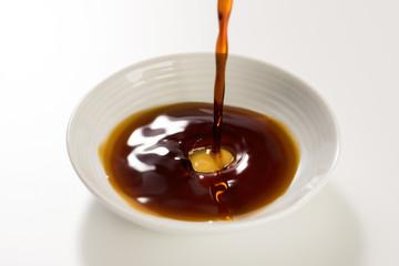豆皿に醤油を注ぐ