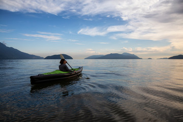 Woman kayaking around the beautiful Canadian Mountain Landscape during a vibrant cloudy evening. Taken in Howe Sound, North of Vancouver, British Columbia, Canada.