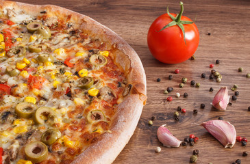Vegetarian pizza and ingredients with spices on rustic board
