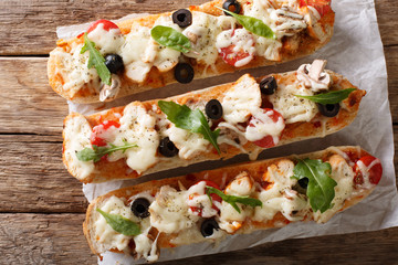 Italian sandwiches pizza casserole: cut baguette baked with chicken, cheese, tomatoes, olives and mushrooms close-up. Horizontal top view