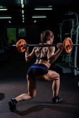 A strong, muscular, girl in black shorts, performs a squat with a barbell and a leg step. Dark gym.