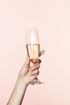 cropped shot of woman cheering by champagne glass isolated on pink background