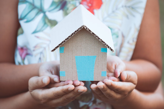 Child and parent holding paper house in hands together as real estate and family home concept