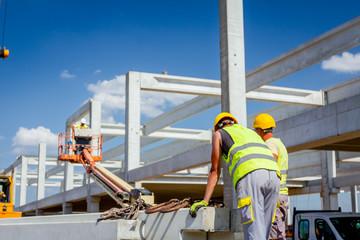 Worker is attaching crane hooks to concrete joist in truck trailer