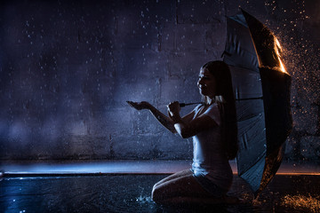 Girl in the white shirt with black umbrella, water drops around and dark walls background illuminated by light during a photoshoot with water