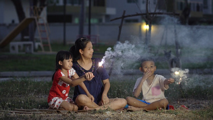 Asian family, mother, son and daughter, fireworks activity at the park.